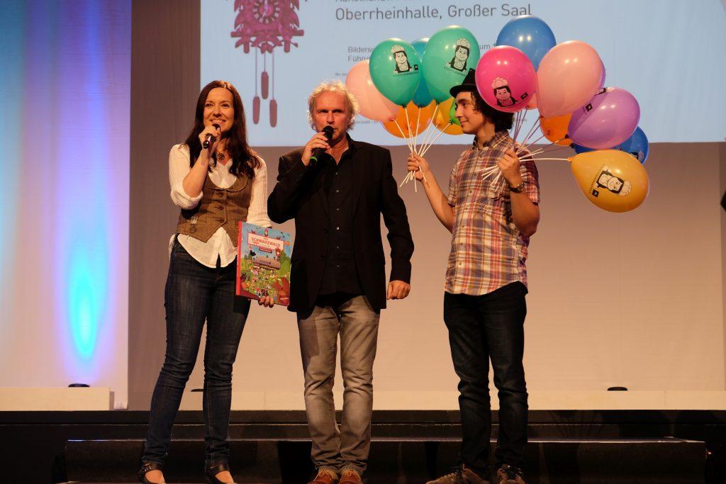 Das Bühnenbild zeigt links Katja Schneider mit Miktofon, mittig Uwe Baumann mit Mikrofon und rechts einen jungen Mann mit bunten Anni-Luftballons