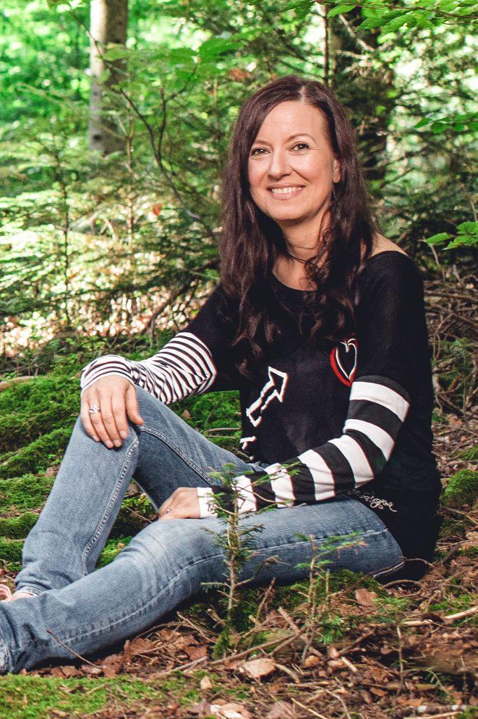 Katja Schneider sitzt mit einem ausgestreckten und einem halb angewinkelten Bein im Wald und schaut mit seitlichem Blick in die Kamera