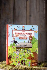 Das Wimmelbuch von Katja Schneider steht aufrecht inmitten von Moos