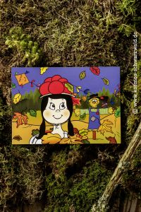 Anni schaut auf dieser Postkarte auf eine Vogelscheuche und im Hinter- und Vordergrund sieht man bunte Blätter, die durch die Luft fliegen sowie ein bunter Drachen