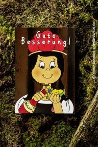 """Auf dieser Postkarte steht """"Gute Besserung"""" und Anni gibt ihrem Freund Federle Medizin aus einer roten Flasche"""