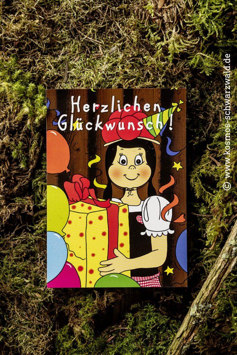 """Auf dieser Postkarte steht """"Herzlichen Glückwunsch"""" und Anni trägt ein Geschenk und es fliegen bunte Luftballons und Luftschlangen durch die Luft"""