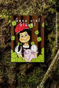 """Auf der Postkarte steht """"Ganz viel Glück"""" und zeigt Anni vor einem Holzbrett mit einem Glücksschweinchen in der Hand und vielen Kleeblättern rund die beiden herum"""