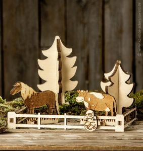 Auf einer massiven Holzplatte steht das Anni-Holzspiel. Dieses besteht aus einem Zaun, dem Pferd Mecki, der Kuh Elsa und zwei Tannenbäumen