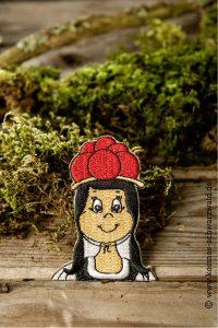 Der Sticker von Anni zeigt das Schwarzwaldmädchen bis zur Brust und liegt auf einem Stück Holz mit Moos im Hintergrund