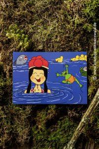 Eine Postkarte zeigt Anni im Wasser mit einem Fisch, einem Frosch sowie fünf teilweise sichtbaren Entenkücken sowie einer halben Seerose