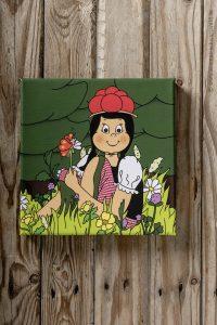 Auf einer quadratischen leinwand sitzt Anni in einer Blumenwiese und hält mit ihrer linken Hand eine Blume mit Schmetterling fest