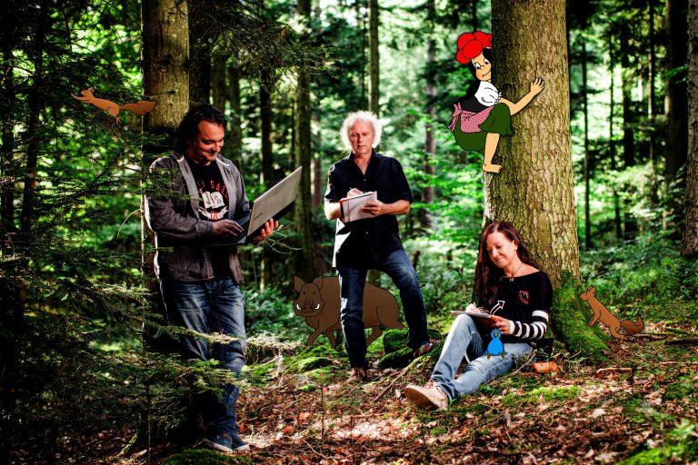Auf dem Bild sind alle drei Autoren von Anni im Wald zu sehen und jeder arbeitet mit Laptop oder Stift und Block während Anni und die Waldtiere die drei Autoren beobachten