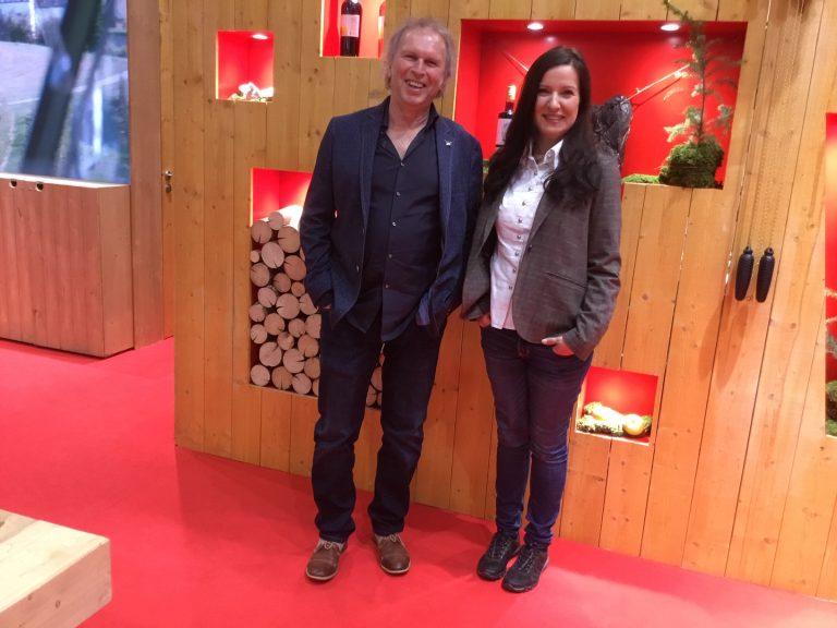 Uwe Baumann und Katja Schneiden stehen in einem Flur vor einer Holzwand nebeneinander und lächeln in die Kamera
