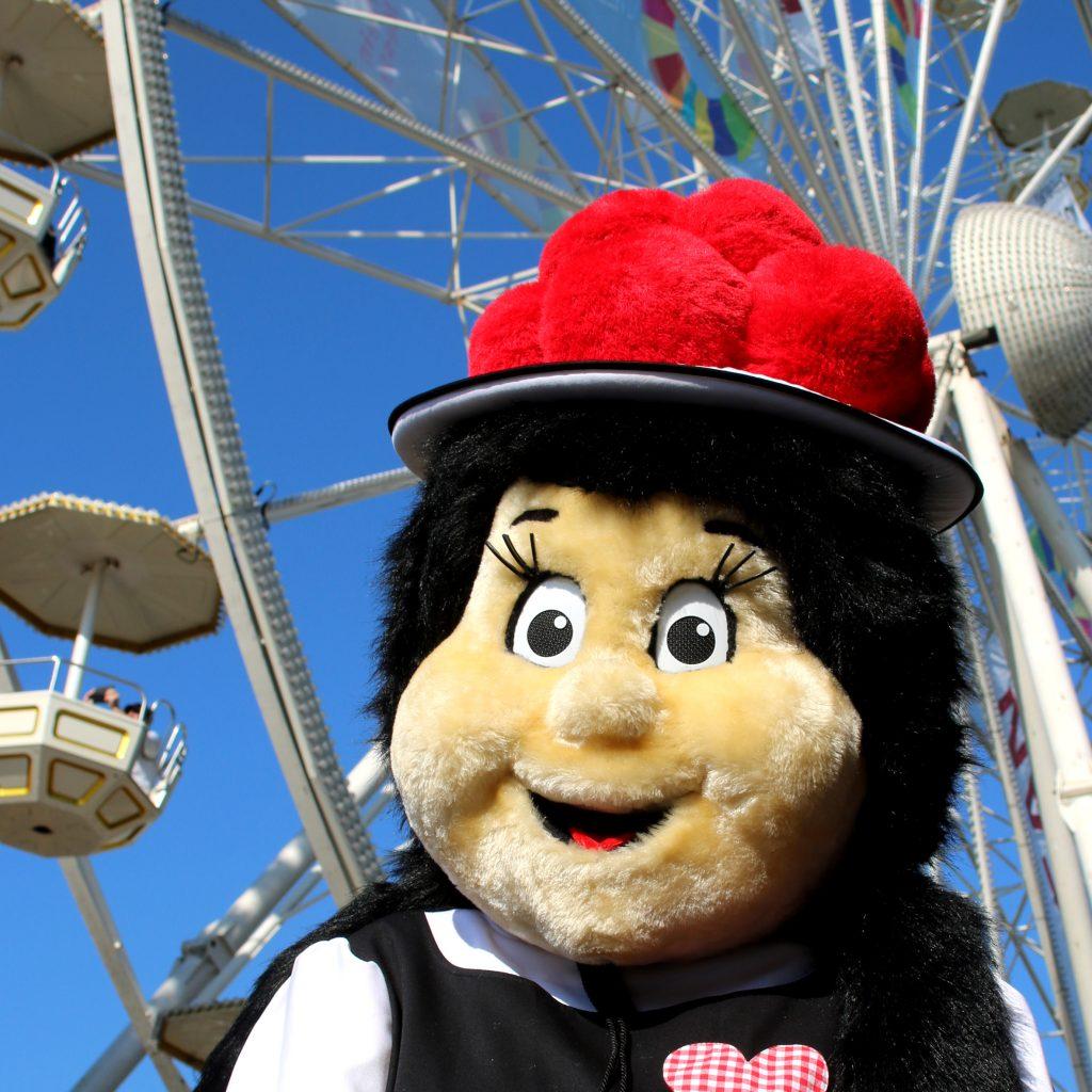 Annis Maskottchen ist aus Stoff, trägt die Tracht und den roten Bollenhut und steht vor einem Riesenrad