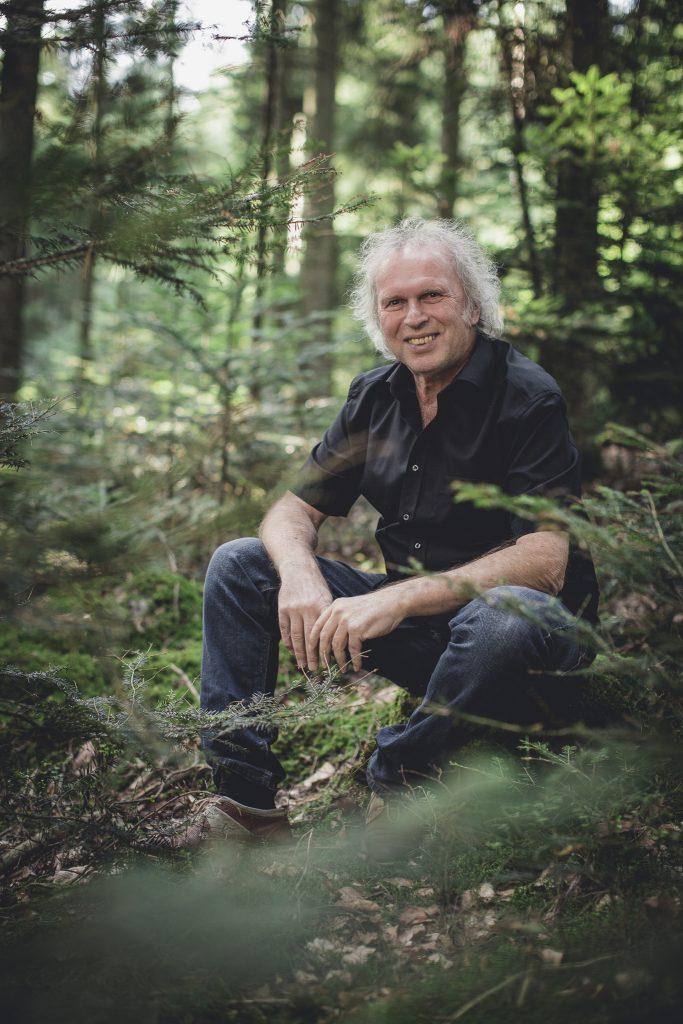 Uwe Baumann sietzt im Wald zwischen Tannenbäumen mit Jeans und schwarzem kurzem Hemd und lächelt in die Kamera