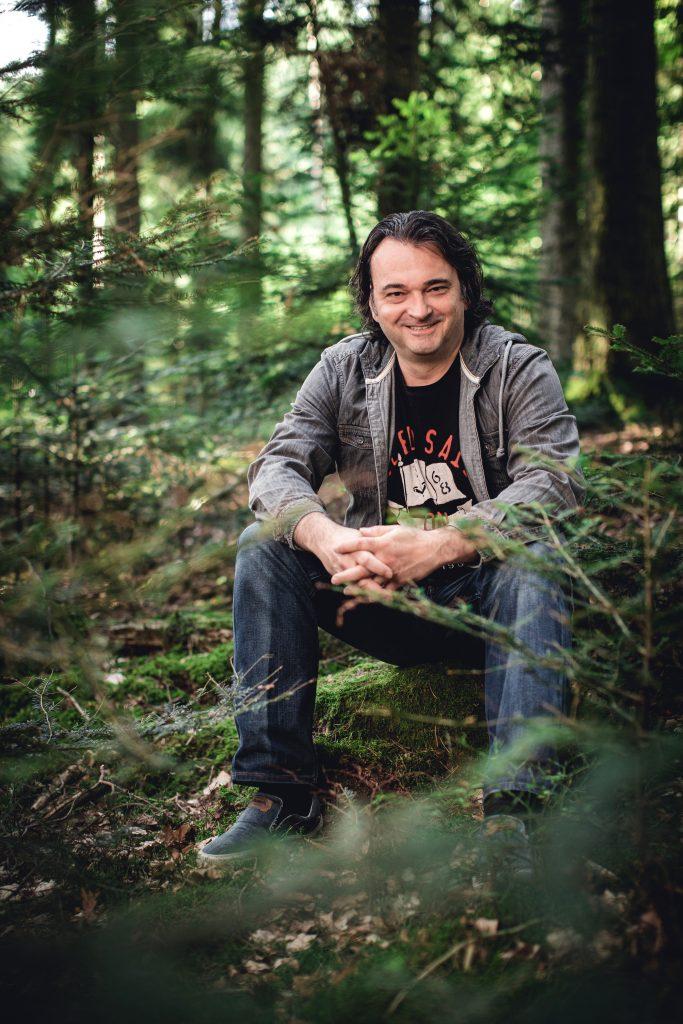Andreas Schneider sitzt mit zusammen gehaltenen Händen im Wald und lächelt in die Kamera