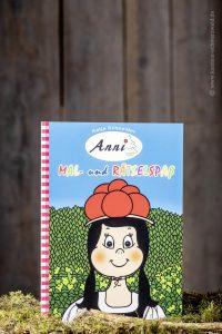 Das Malbuch von Anni steht aufrecht inmitten von Moos und Holz