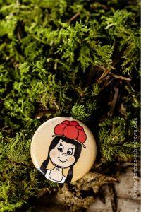Der Button zeigt Anni bis zur Brust und liegt auf Grünzeug und Holz