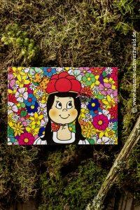 Auf dieser Postkarte ist Anni vor ganz vielen bunten Blumen zu sehen