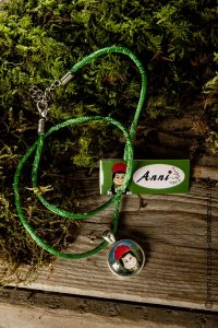 Eine Halskette von Anni mit grünem Band und einem Bild von Anni liegt mit Etikett auf Holz und Grünzeug