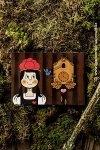 Auf dieser Postkarte beobachtet Anni ihren Freund Federle, der aus einer Kuckucksuhr herauskommt